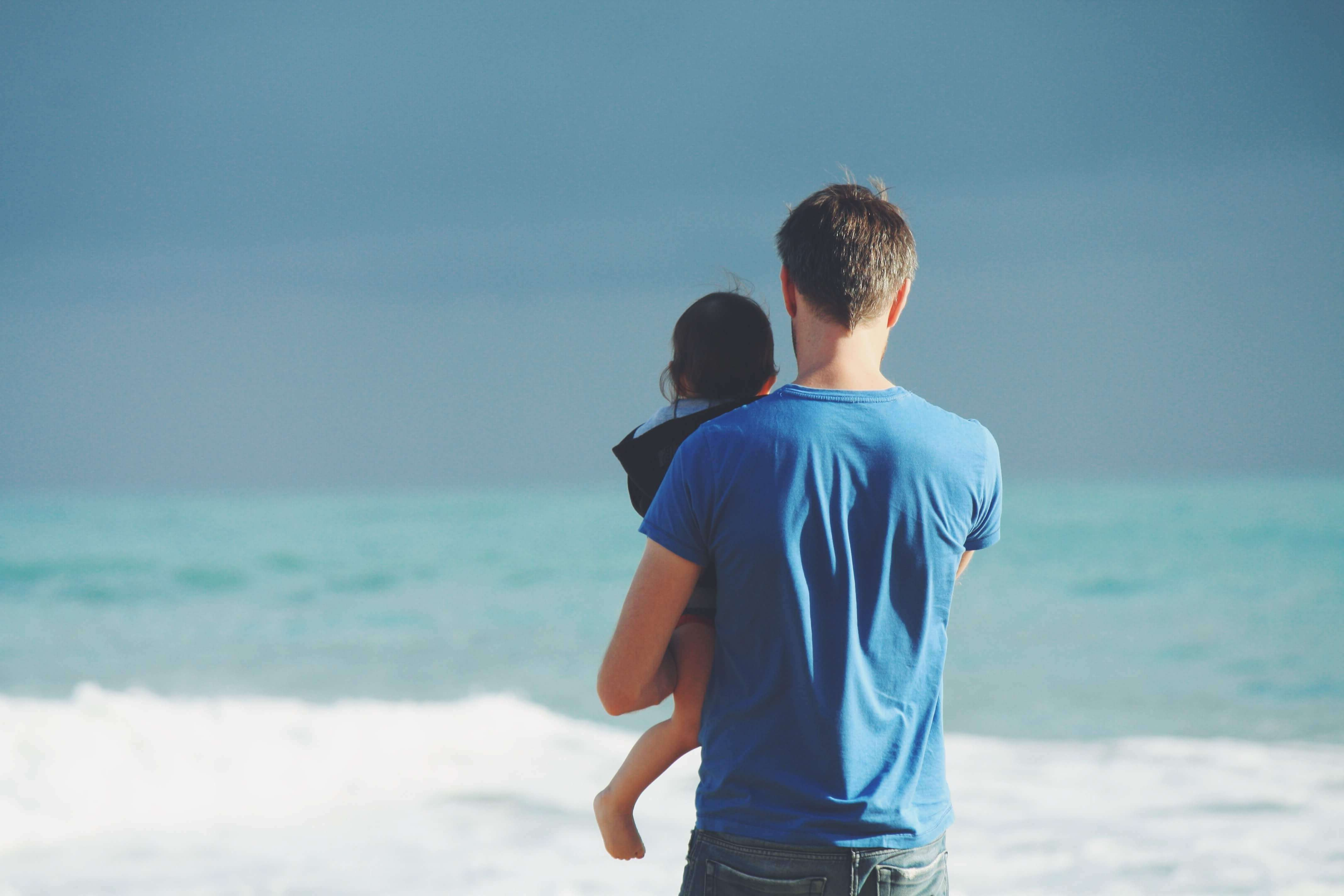 Man holding infant infront of a beach
